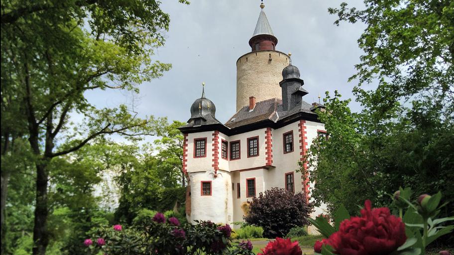 Burg Posterstein vom Park aus gesehen mit blühenden Rhododendren und Pfingstrosen.